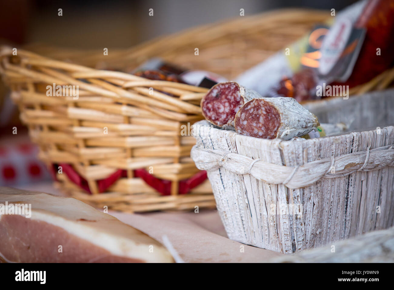 Traditional home-made salami in the basket on the market for sale. - Stock Image