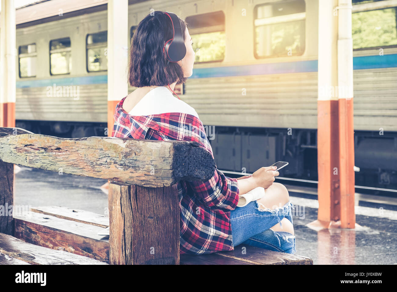 Young travel sitting at railway platform and listen music waiting her train for travel alone travel and summer concept