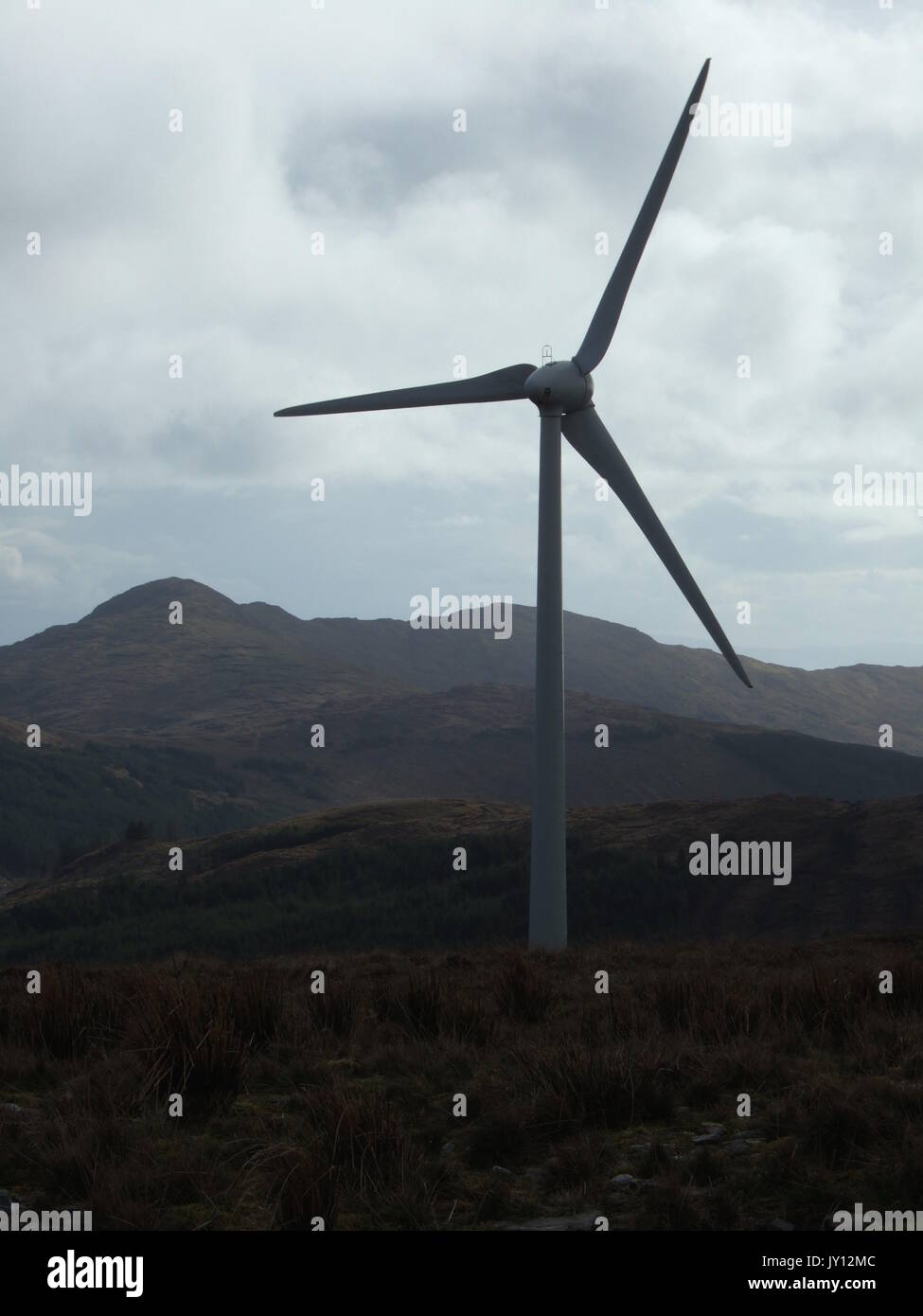 Wind turbines pictured in Donegal August 11th 2017.  Wind energy or wind power describes the process by which wind is used to generate electricity. Wind turbines convert the kinetic energy in wind to electricity by rotating propeller-like blades around a rotor. The rotor turns the drive shaft, which turns an electric generator. Three key factors affect the amount of energy a turbine can harness from the wind: wind speed, air density, and swept area. Renewable energy is energy that is collected from renewable resources, which are naturally replenished on a human timescale, such as sunlight, win - Stock Image