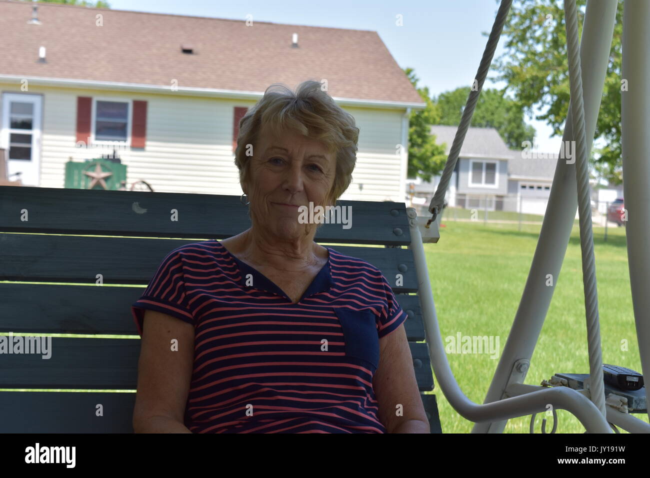 Elderly woman sitting on a swing in her backyard smiling. She doesnt seem to have a care in the world on this beautiful sunny day! - Stock Image