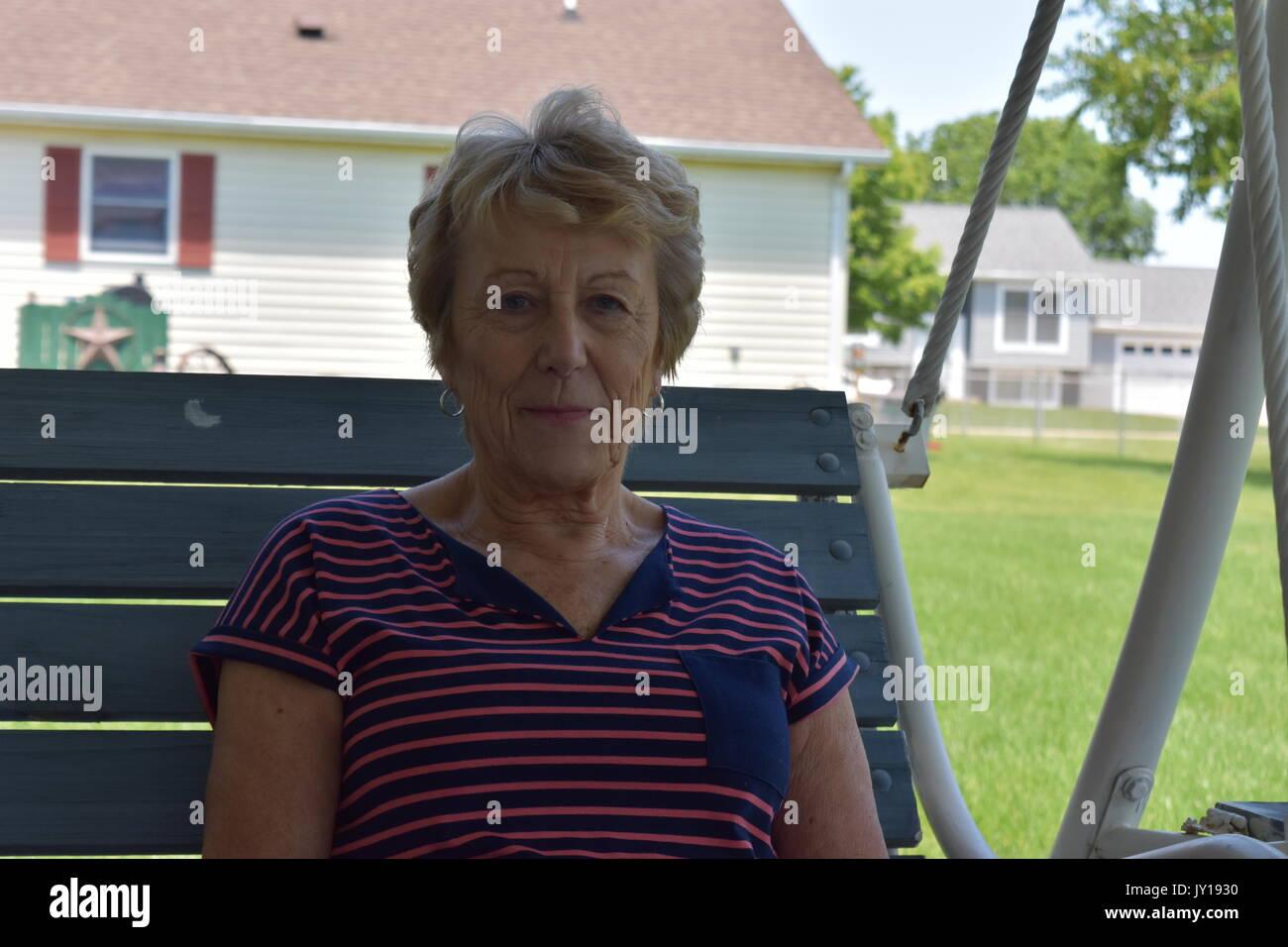 Elderly woman sitting on a swing in her backyard - Stock Image