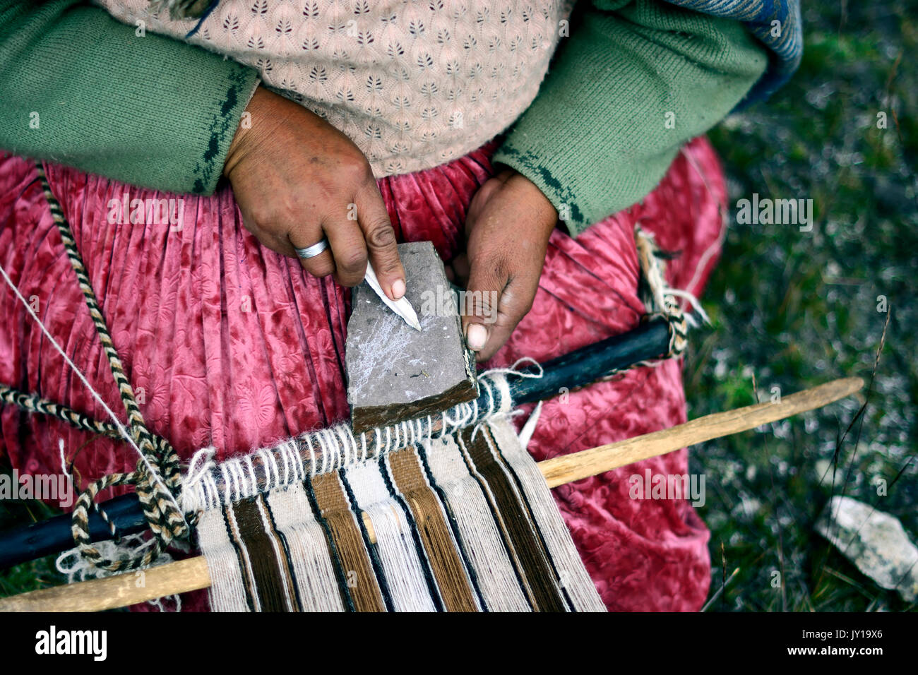 woman working on a traditional weaving loom in Peru Stock Photo
