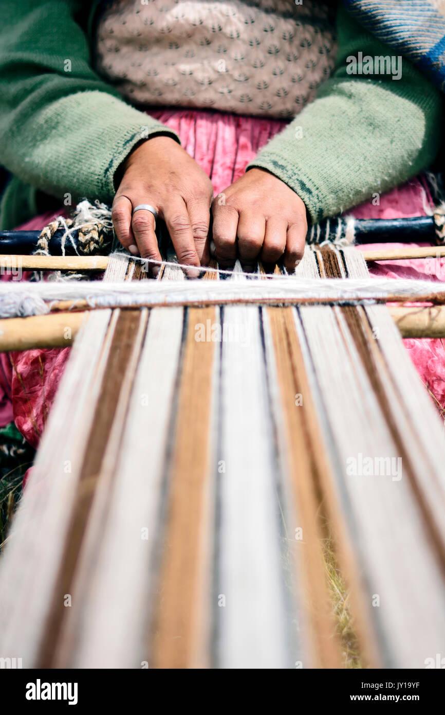 Quechua woman using a weaving loom in Peru - Stock Image