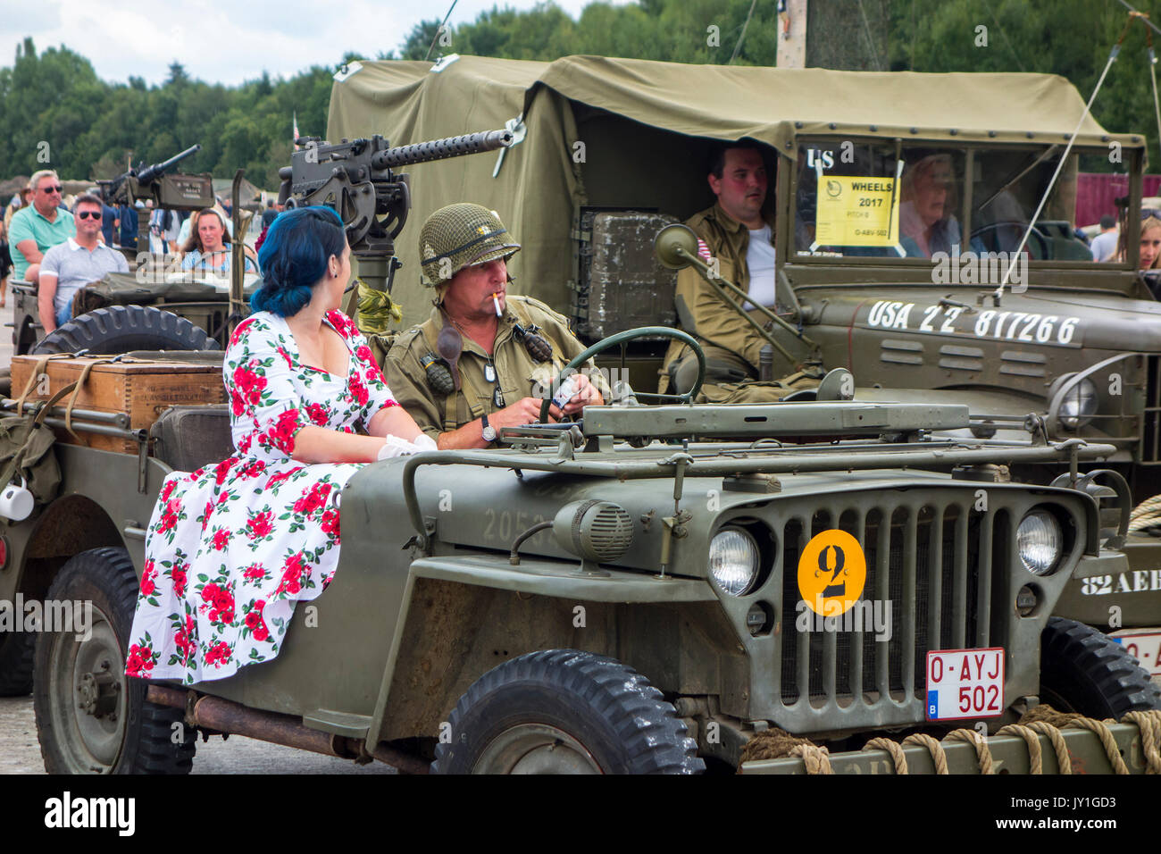 Reenactors dressed as WW2 US soldier and woman in 1940s dress posing in WWII military Willys MB jeep during World War Two militaria fair - Stock Image