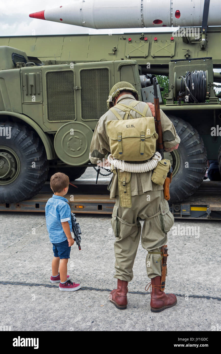 Little boy with toy gun and WW2 reenactor in US soldier outfit looking at missile truck at World War Two militaria fair - Stock Image