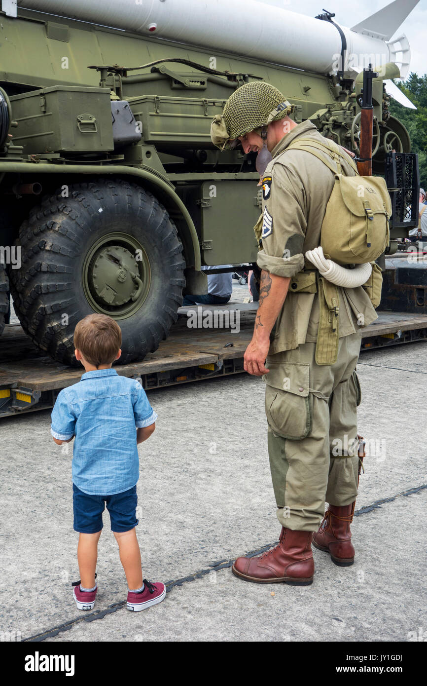 Little boy and WW2 reenactor in US soldier outfit looking at missile truck at World War Two militaria fair - Stock Image