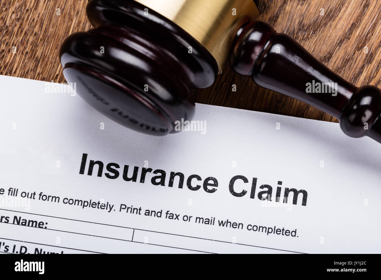 Close-up Of Wooden Gavel On Insurance Claim Form At Wooden Desk - Stock Image