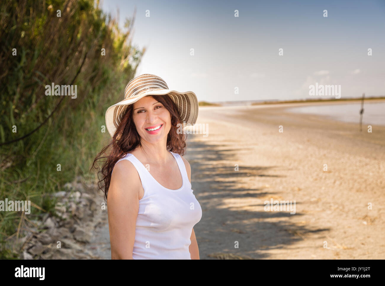 Handsome Mature Busty Woman In Very Good Shape With Wide Hat Smiling On A Sun Split
