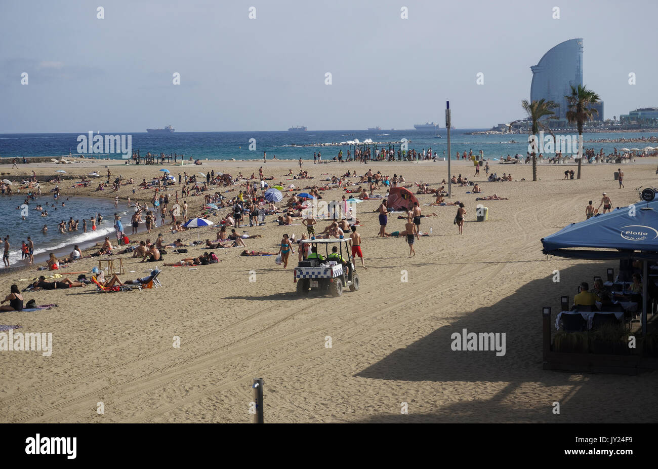 Guardia Urbana police car with policemen patrolling by the sandy crowed beach securing beach safety. - Stock Image