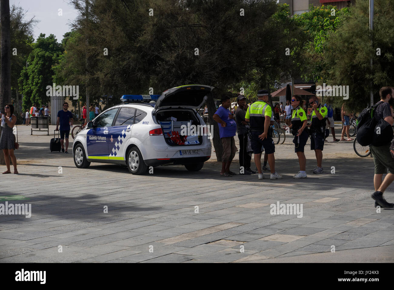 Guardia Urbana policemen by the crowed beach securing beach safety. - Stock Image