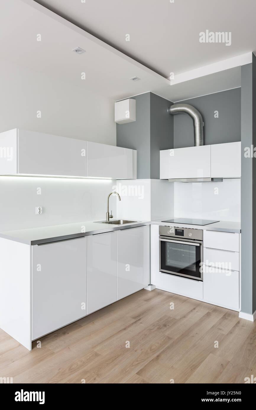 Small, modern, white kitchen with wooden floor panels Stock Photo ...