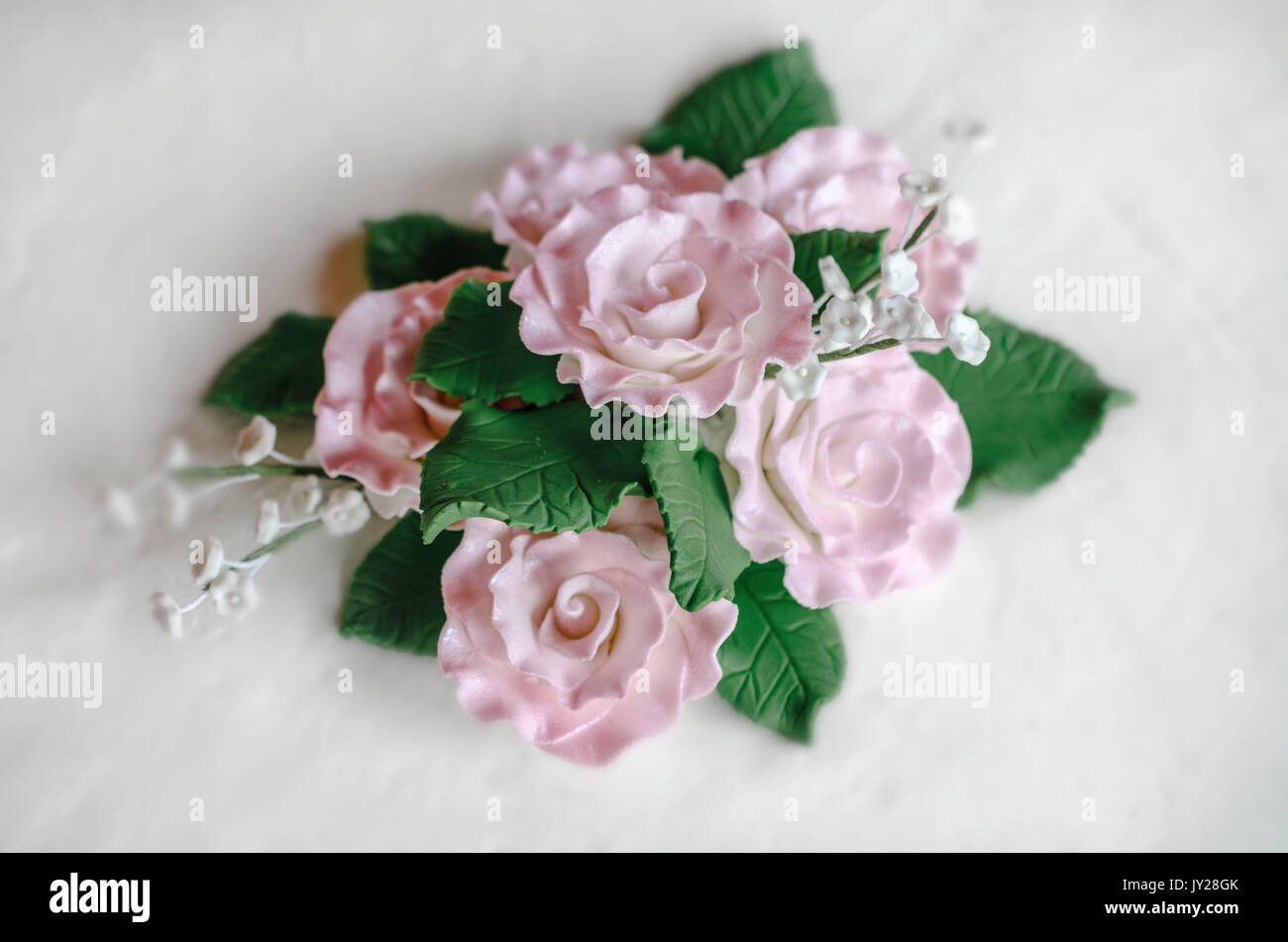 Fondant shaped like pink flowers and green leaves - Stock Image