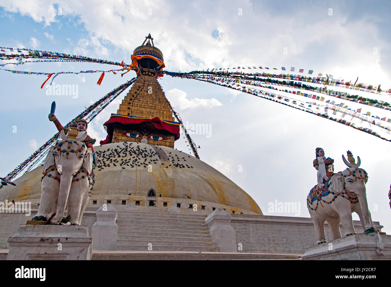 Back lit Bodhnath Stupa Temple and statues with overcast day. Boudhanath Stupa is the largest stupa in Nepal and the holiest Tibetan Buddhist temple o - Stock Image