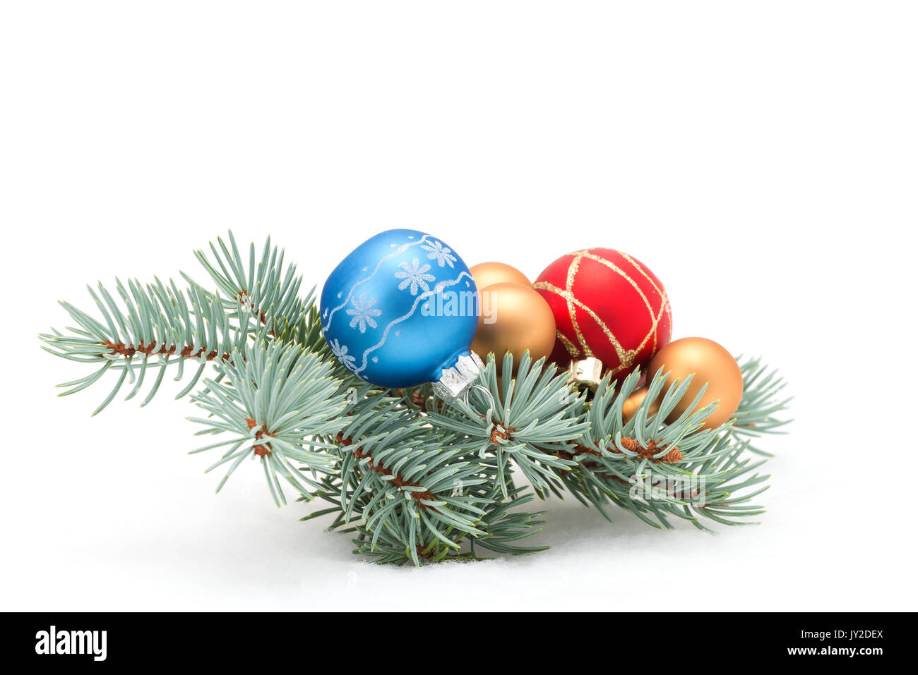Colorful christmas baubles on a fresh spruce bough. - Stock Image