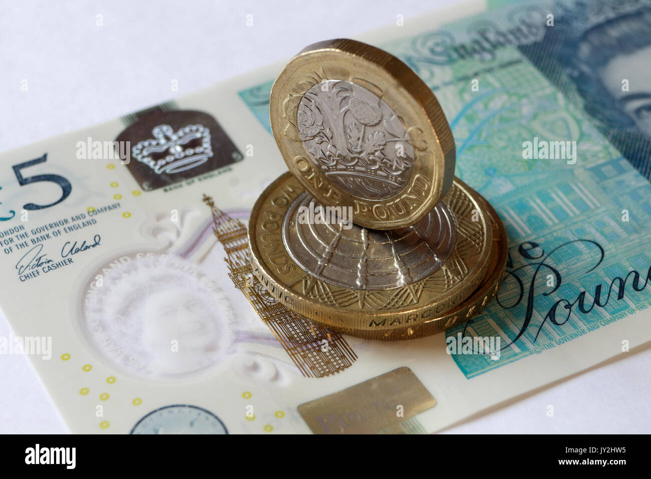 New Pound coin and five pound note - Stock Image