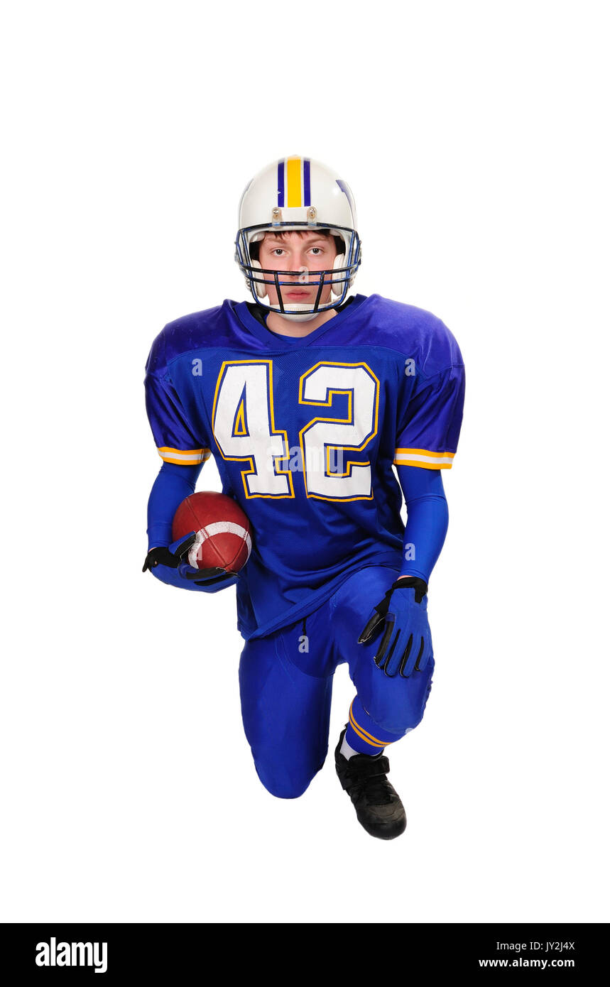 Teenage High School Football Quarterback kneels with football shot on white background. - Stock Image