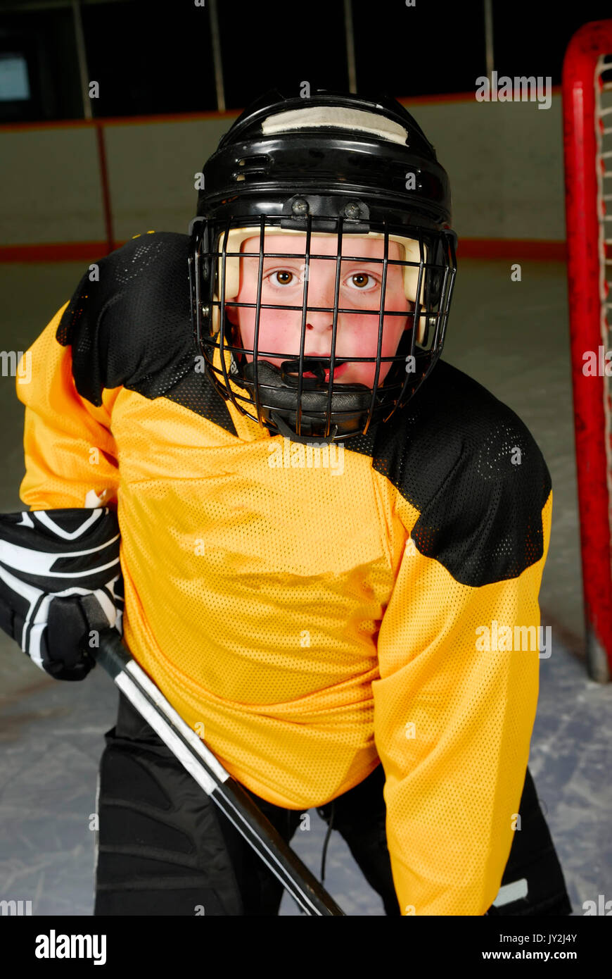 Closeup of a peewee hockey player in his mask. - Stock Image