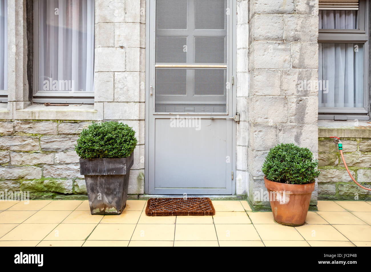 On the inner courtyard there are two flower pots with plants next to ...