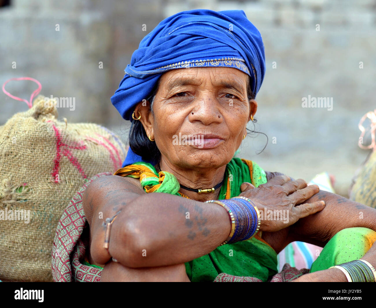 Closeup street portrait of an elderly Indian Adivasi market woman with blue headwrap and blue bangles. - Stock Image