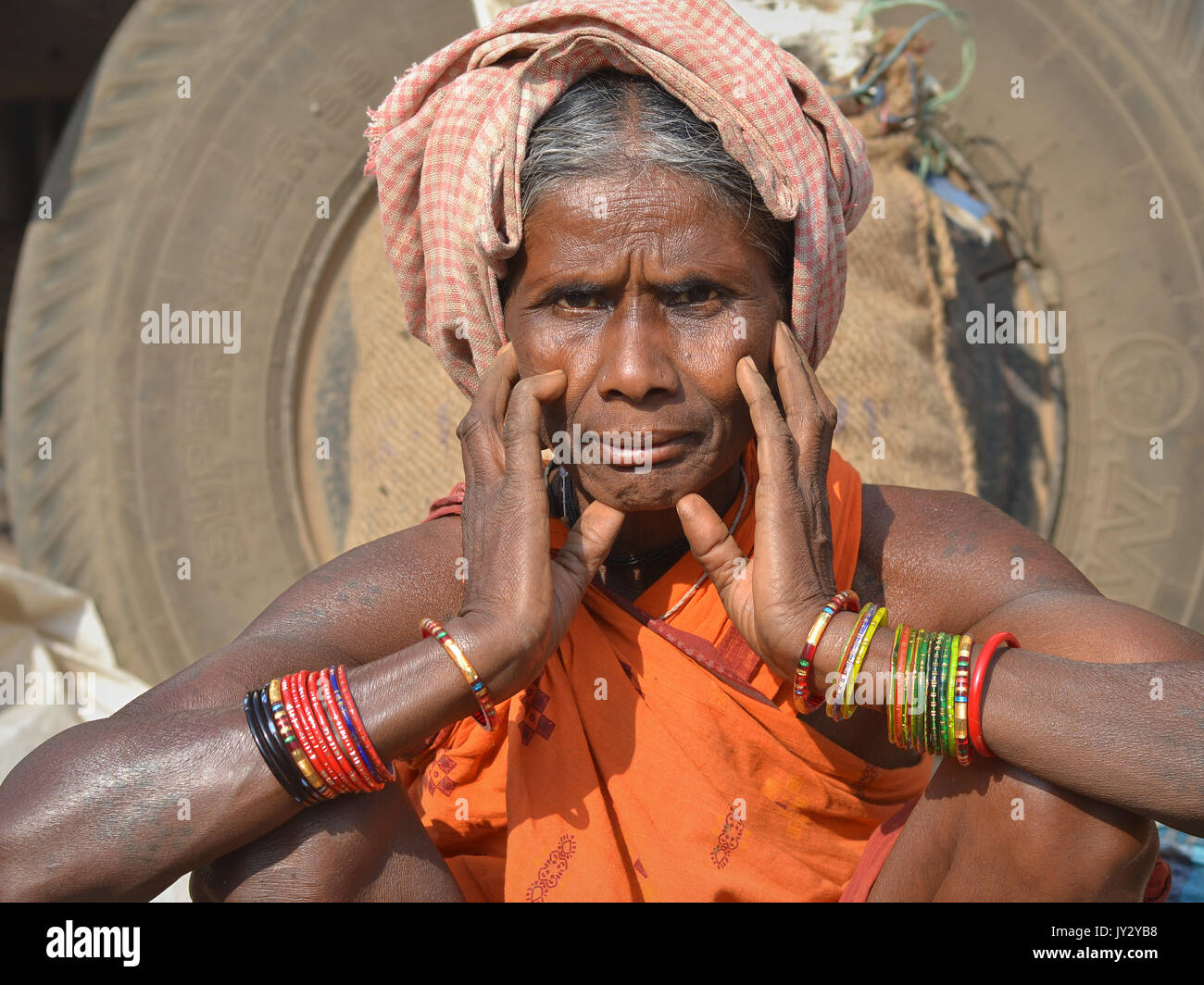 Closeup street portrait of an old Indian Adivasi market woman, resting her chin on her hands (...and showing her - Stock Image