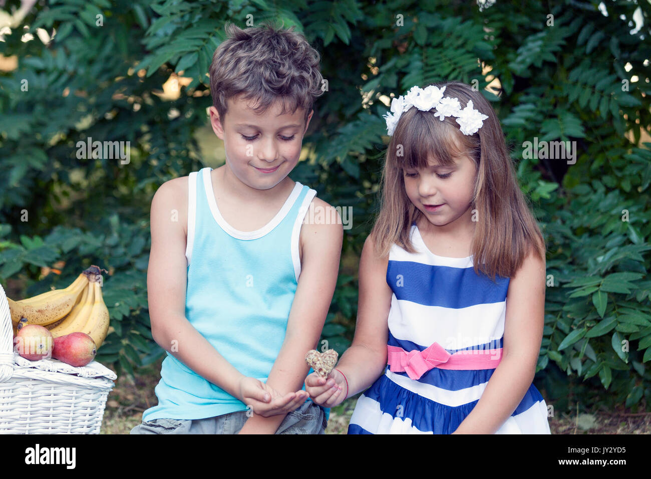 little cute boy and girl sit in the grass and play. the little girl