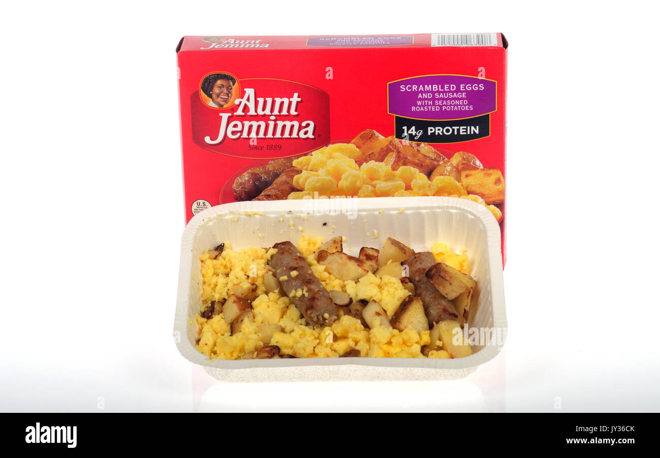 Tray of microwaved Aunt Jemima Frozen breakfast of scrambled eggs, sausage and roasted potatoes  with packaging on white background. USA - Stock Image