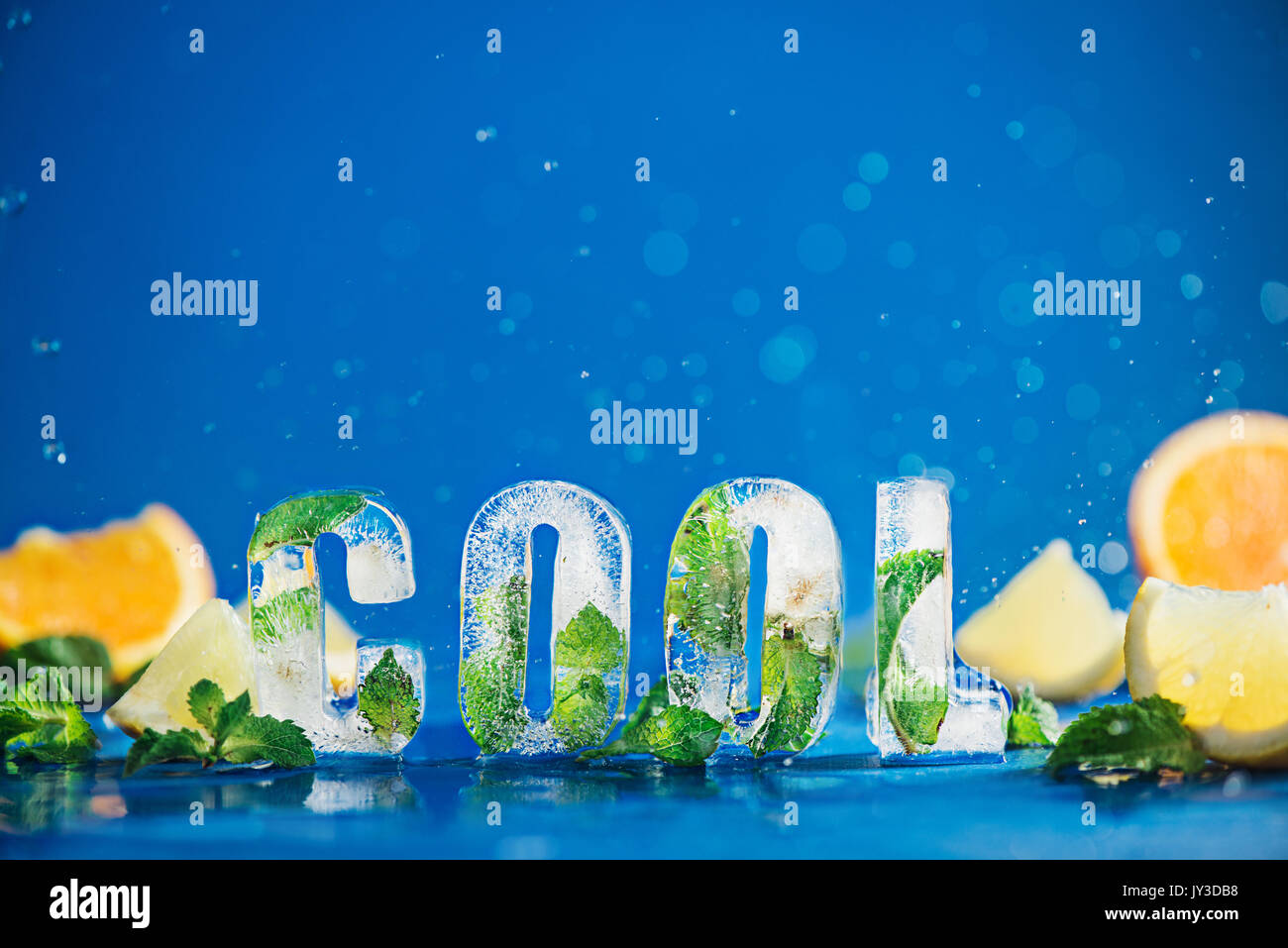 Ice cube lettering with frozen mint leaves, lemon slices and oranges on a blue background with water splashes. Text says Cool. - Stock Image