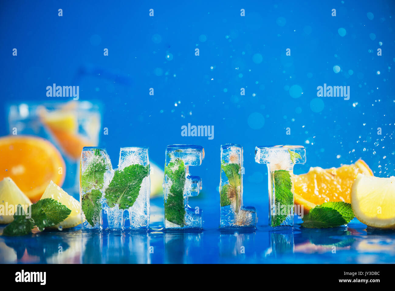 Ice cube lettering with frozen mint leaves, lemon slices and oranges on a blue background with water splashes. Text says Melt. - Stock Image