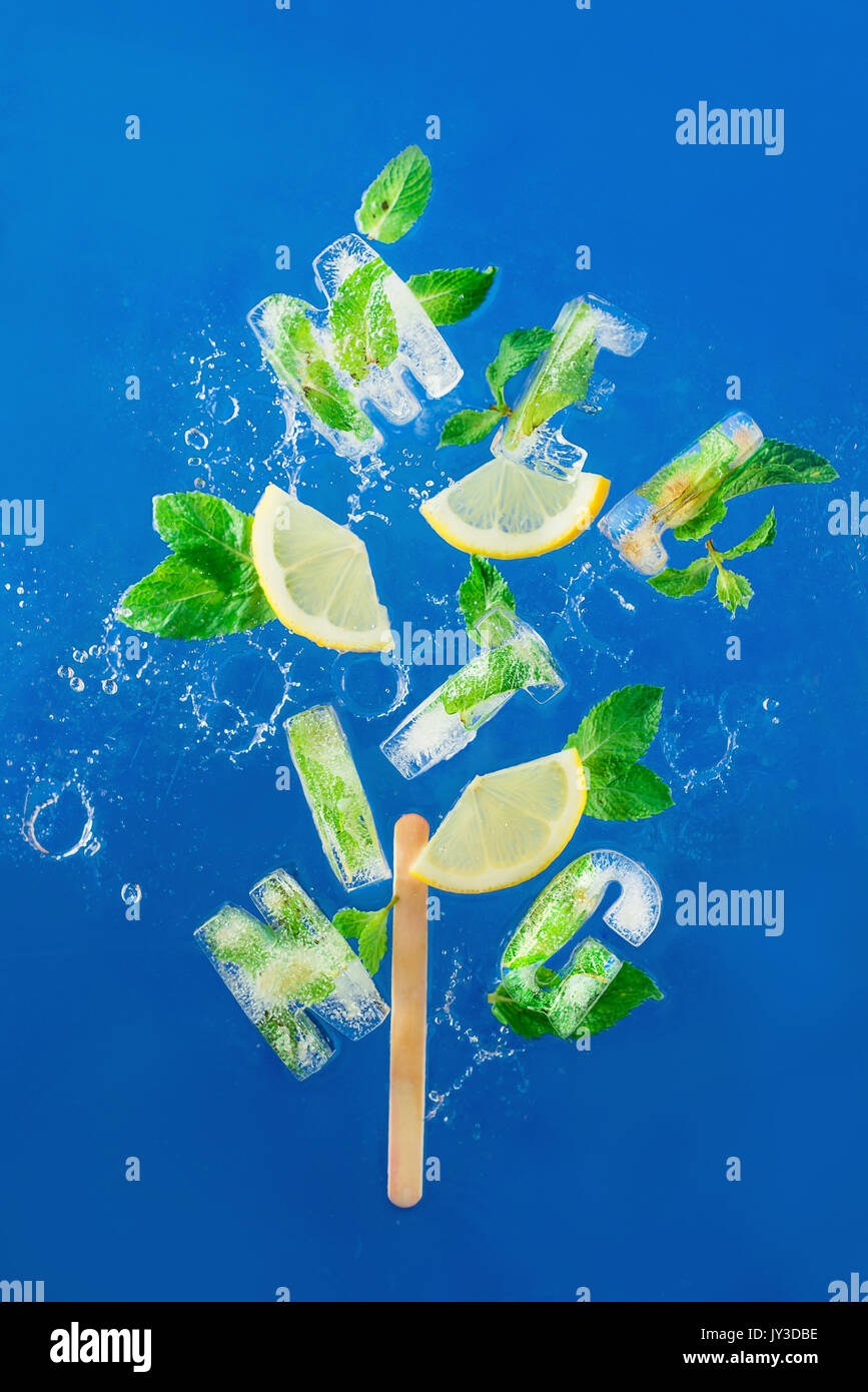 Ice cube lettering with frozen mint leaves, lemon slices and oranges on a blue background with water splashes. Text says Melting. - Stock Image
