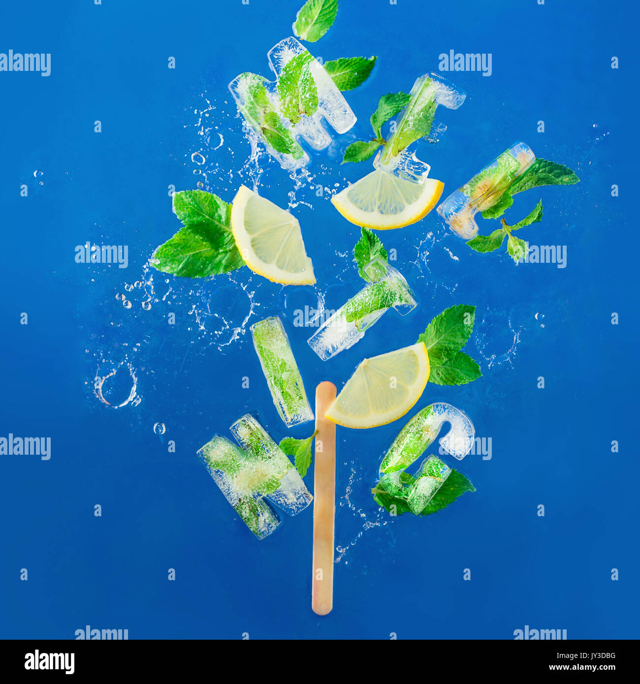 Ice cube lettering with frozen mint leaves, lemon slices and oranges on a blue background with water splashes. Text says Aloha - Stock Image
