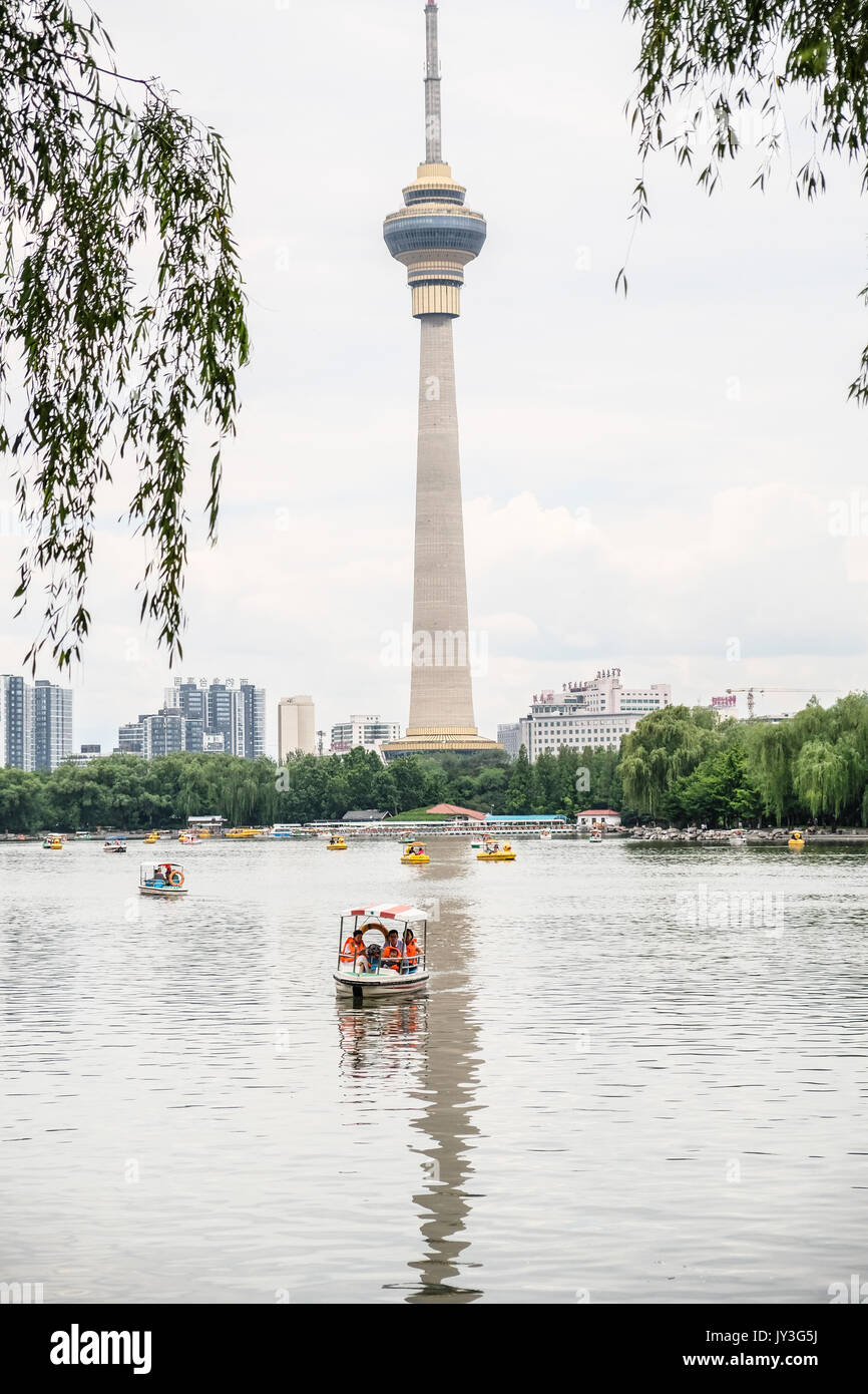 The CCTV tower reflected on Yu Yuan Tan lake, scattered with rented boats - Stock Image