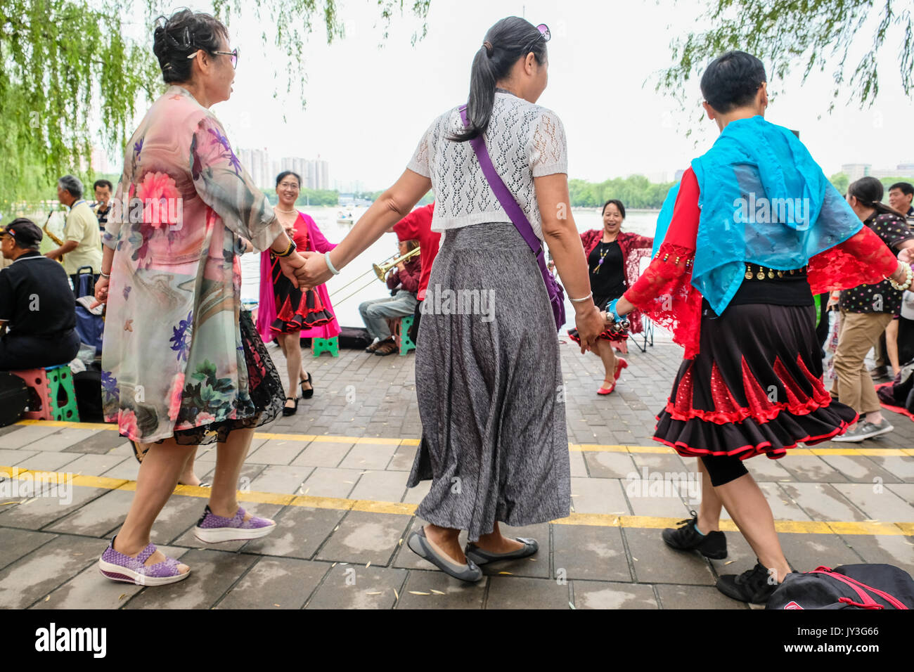 Retired Chinese men and women holding hands and dancing in the park - Stock Image