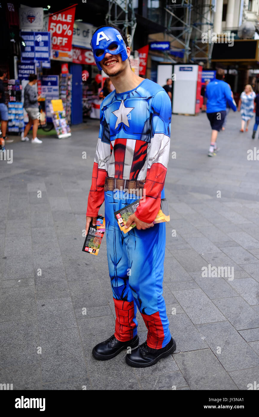 A smiling guy dressed as Captain America giving out vouchers to Planet Hollywood in Leicester Square in London's West End. - Stock Image