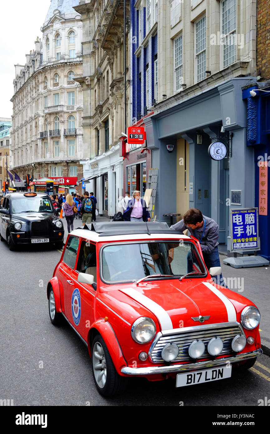 A classic mini car with one of London's famous black taxis behind it, in Wardour Street, Soho near Chinatown, London - Stock Image