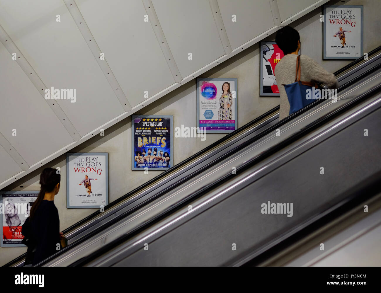 PAssengers reading the advertising panels on the wall of the escalator at a London Underground Station - Stock Image