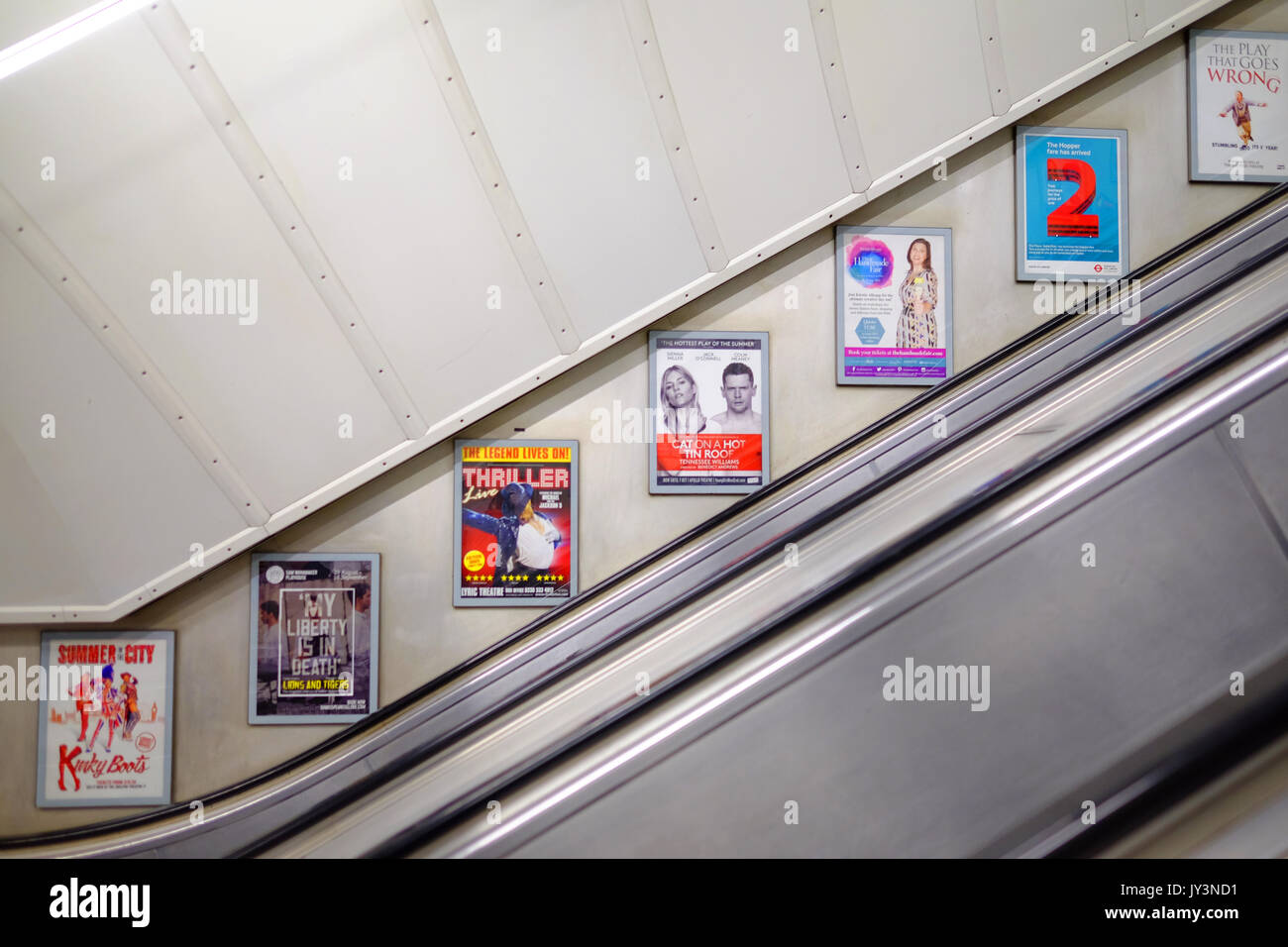 The advertising panels on the wall of the escalator at a London Underground Station. - Stock Image