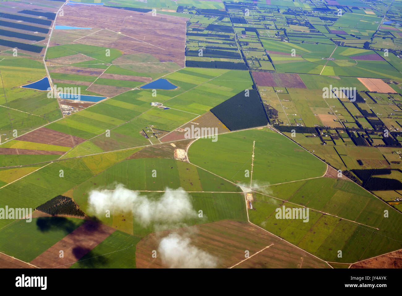 Closeup aerial view of Canterbury Plains as the mist clears on an Autumn morning, New Zealand. In the background are the Southern Alps. Stock Photo
