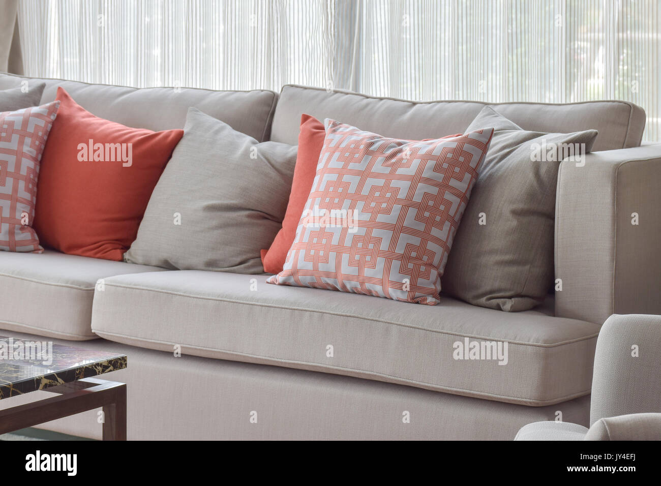 Chinese pattern pillow, red and gray pillows setting on light gray comfy sofa - Stock Image