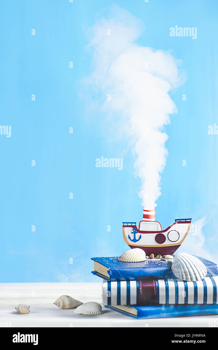 Steam engine papercraft. Still life with tiny steamboat on a pastel blue background. Stock Photo