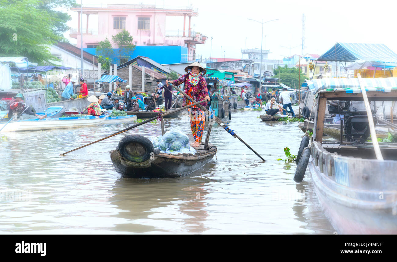 Ferryman rowing takes visitors across  river to visit floating market, this is main transportation in river water festival Lunar New Year - Stock Image