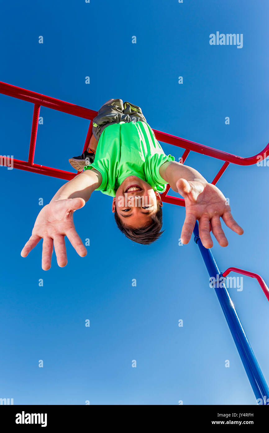 A happy young boy hangs upside down from the monkey bars. - Stock Image