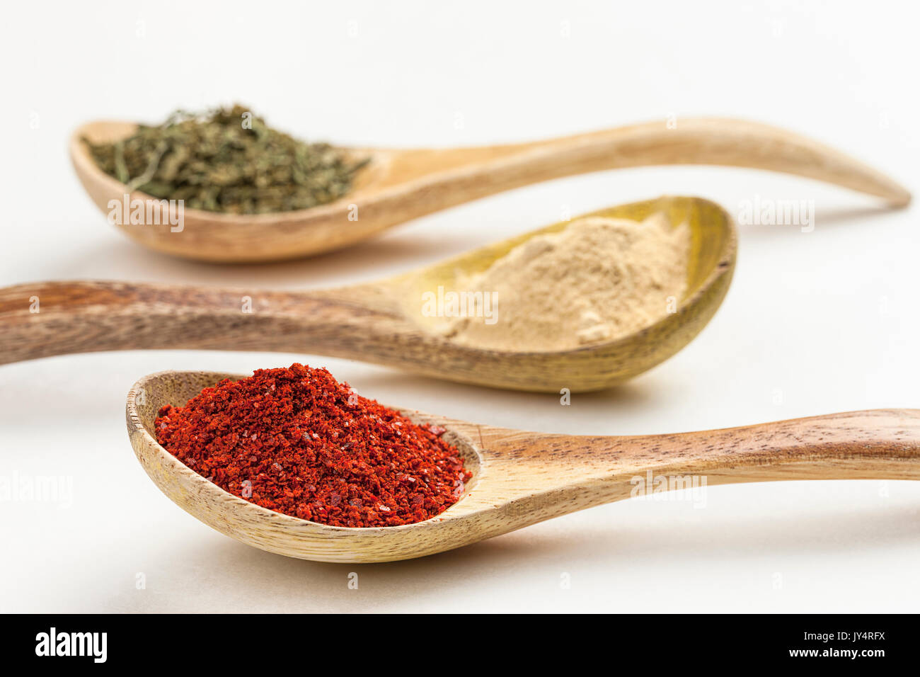 A close up of wooden spoons filled with red pepper powder, garlic powder, and basil leaves. - Stock Image