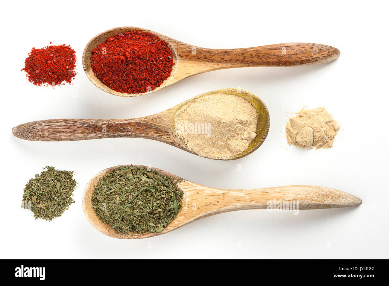An overview of wooden spoons filled with red pepper powder, garlic powder, and basil leaves. - Stock Image