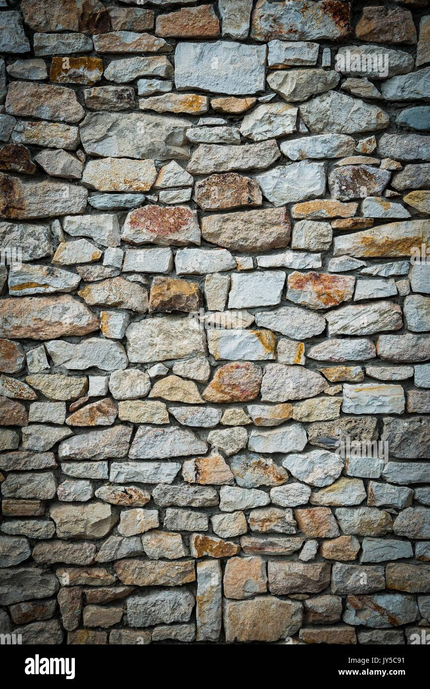 Stone wall background of colorful stones. Vignetted borders. Vertical photo - Stock Image