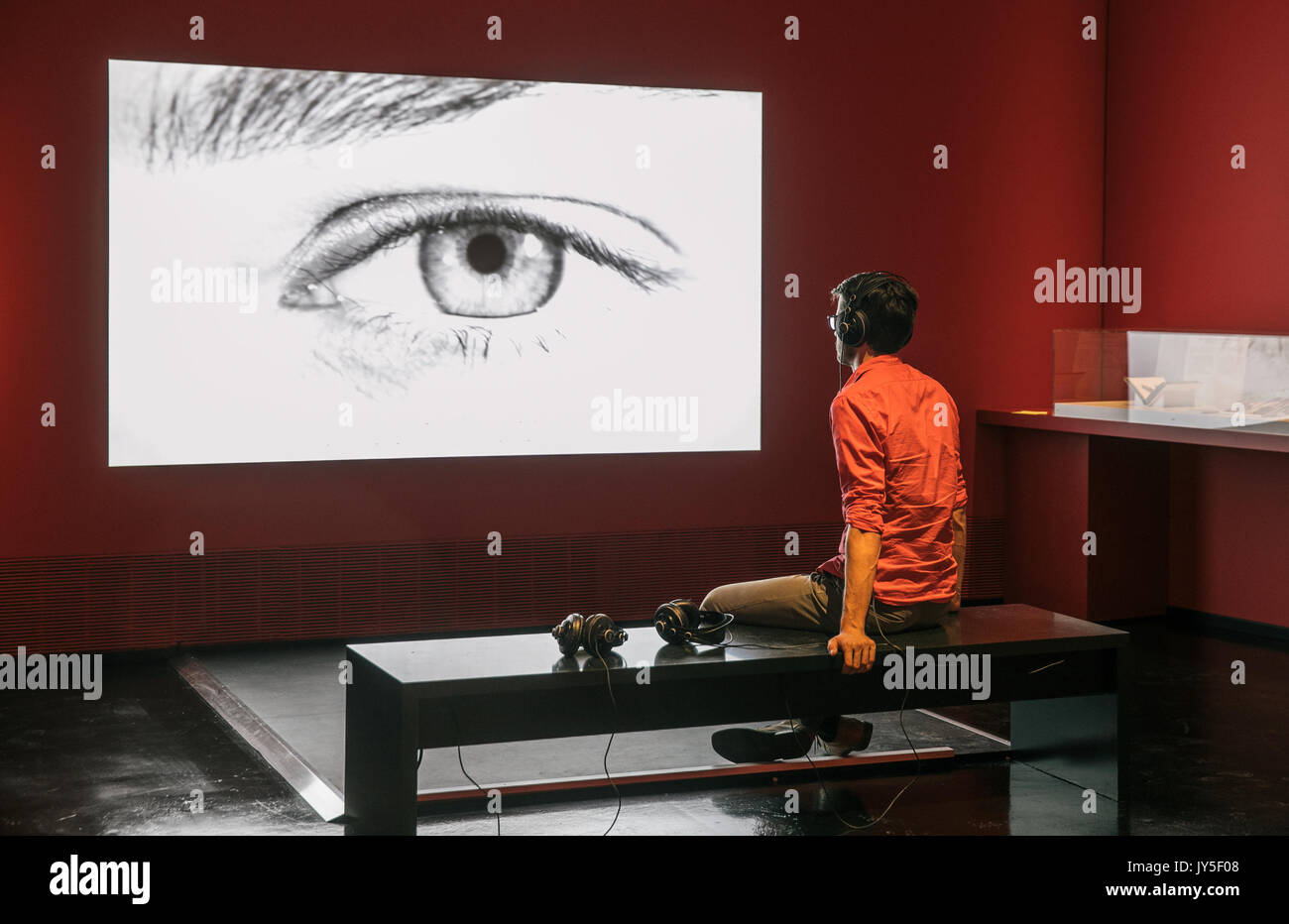 Dresden, Germany. 17th Aug, 2017. A man looking at the projection of an eye in an exhibition room of the new exhibition 'The face. A search for clues' ('Das Gesicht. Eine Spurensuche') in the German Hygiene Museum in Dresden, Germany, 17 August 2017. The exhibition takes place between 19 August 2017 and 25 February 2018. Photo: Oliver Killig/dpa-Zentralbild/dpa/Alamy Live News - Stock Image