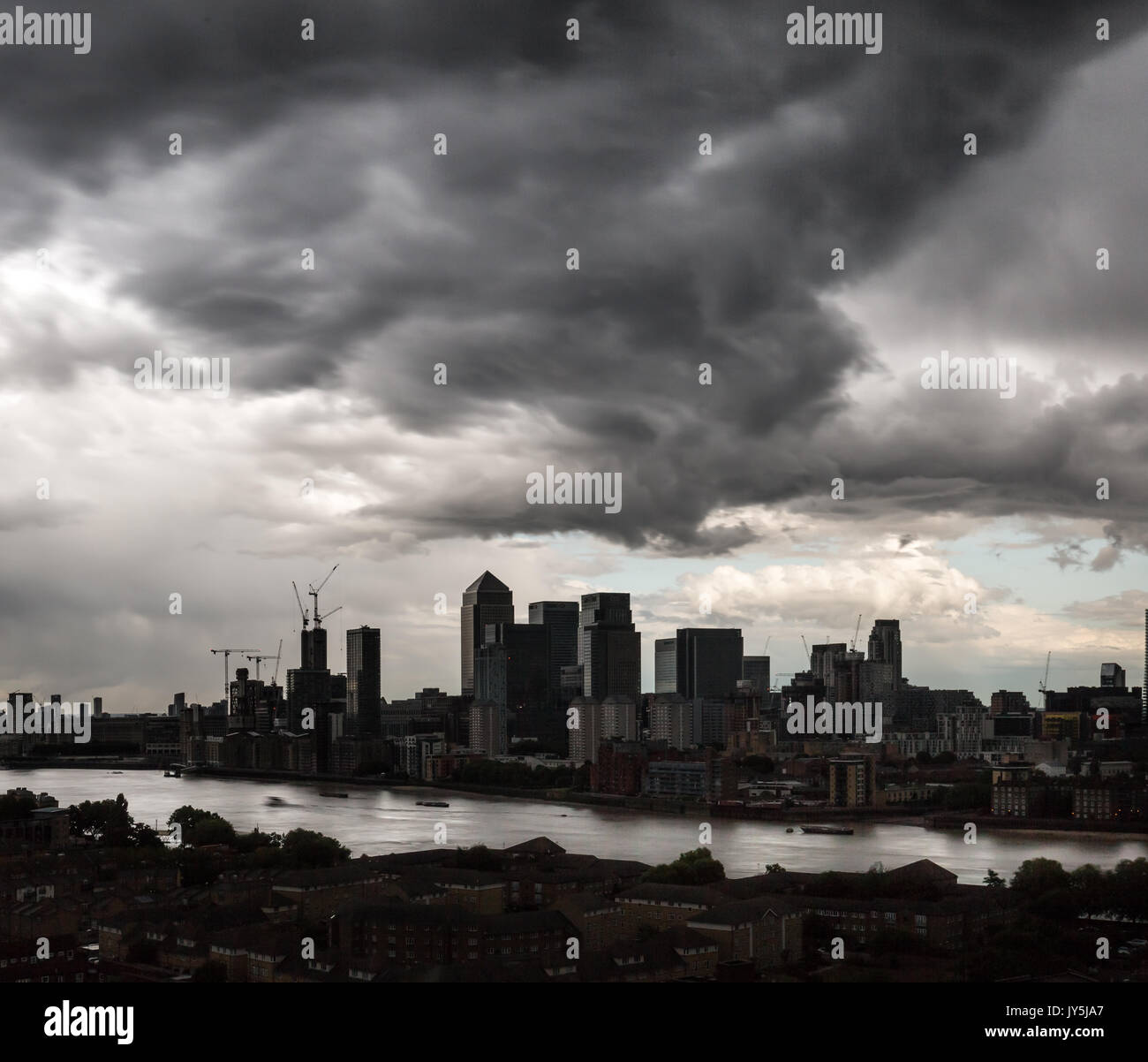 London, UK. 18th Aug, 2017. UK Weather: Dark afternoon storm clouds over Canary Wharf business park buildings Credit: Stock Photo