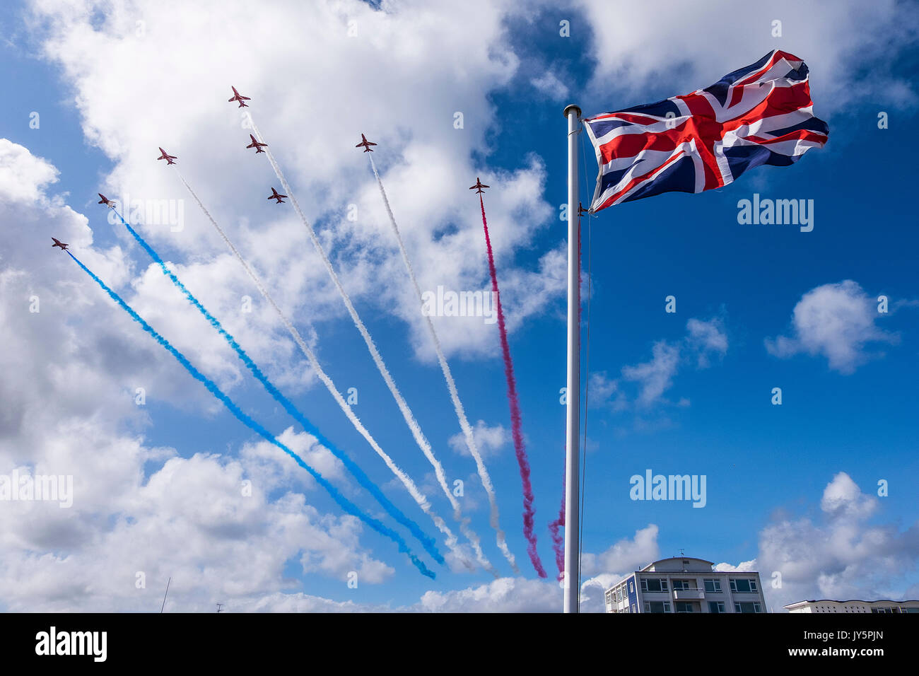 Eastbourne, England, UK. 18th August 2017. Day 2 of Airbourne, the popular south coast seaside airshow on its 25th anniversary. The Red Arrows RAF aerobatic team arrive, overflying a union flag on the Martello Tower on Eastbourne seafront. Credit: Malcolm Park / Alamy Live News - Stock Image