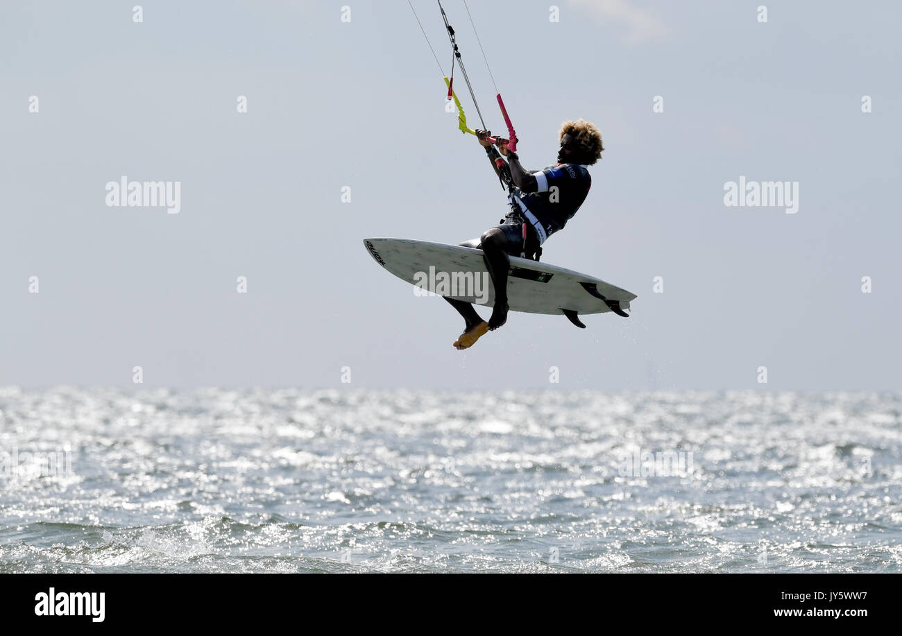 Fehmarn, Germany. 19th Aug, 2017. The Kite-Surfer Mitu Monteiro of Cap Verde shows a jump in the 'Strapless Freestyle' competition during the Kitesurf World Cup at Fehmarn, Germany, 19 August 2017. Until the 27 August 2017 around 70 participants of 19 nations compete for the title in various disciplines. Approximately 100.000 spectators are being expected. Photo: Carsten Rehder/dpa/Alamy Live News - Stock Image