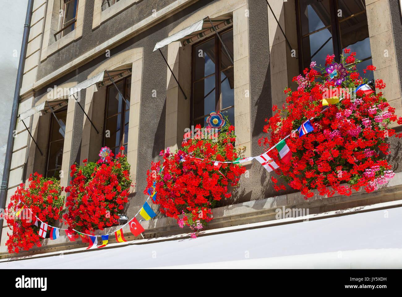 Vintage window with flowers and flags, Geneva, Switzerland - Stock Image