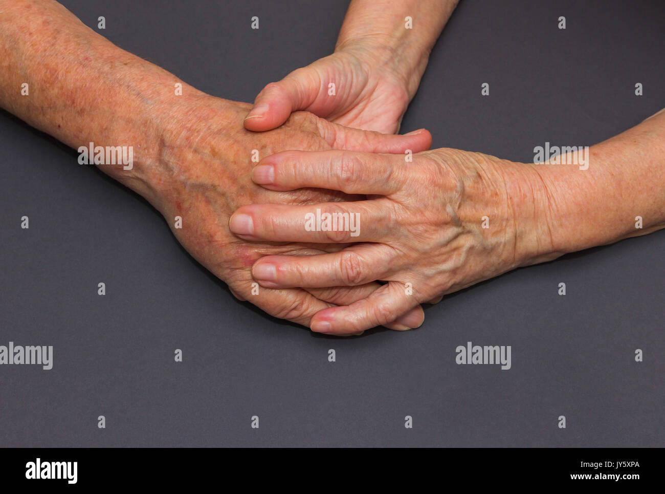 Hands of two loving senior people on a dark background - Stock Image